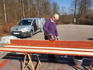Kent-Arne målar plankor till staket för Tjäderstigen